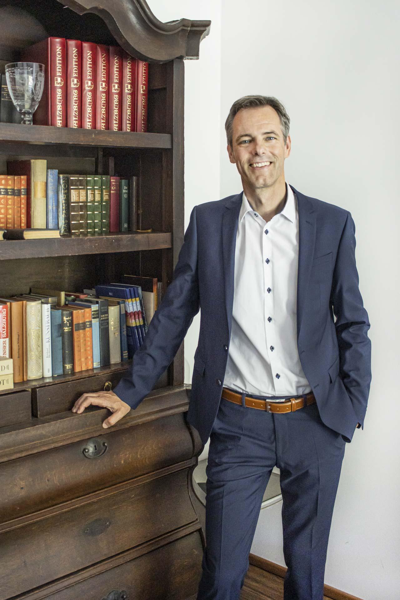 Hannes Abfalterer in seinem Büro vor antikem Kasten